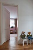 Children's chairs with carved, painted, animal backrests next to open door leading to child's bedroom