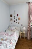 Child's bed with white wooden frame, bedside table and red and white striped curtains