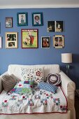 Patchwork blanket and scatter cushions on armchair bed below pictures on blue-painted wall