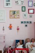 Dolls in dolls' pram below framed pictures and marionettes on pink-painted wall