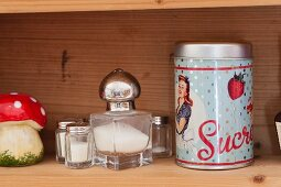 Various salt cellars and vintage sugar tin on wooden shelf