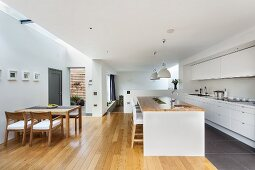 Open-plan designer kitchen - dining area with wooden table and chairs, island counter and fitted kitchen