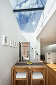Dining table and chairs made from pale wood below skylight with view of blue sky