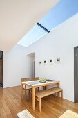 Wooden table and bench set below skylight