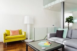 Lounge area with pale grey couch, yellow armchair and designer standard lamp