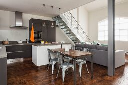Open-plan interior in shades of grey with dining area, pale grey sofa and metal staircase