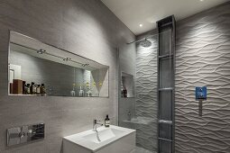 Designer bathroom - washbasin against tiled wall, mirror in niche, shower area with 3D structured tiles on wall