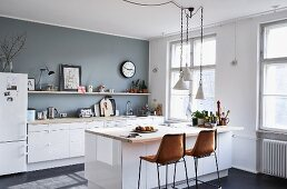 Counter with retro bar stools in simple kitchen with accent wall painted grey