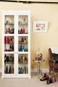 Ladies' shoes in white display case next to high heels under glass cover on side table and armchair against wall painted pale yellow