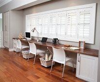Office for three people in window niche in hallway; storage baskets on castors below long desk