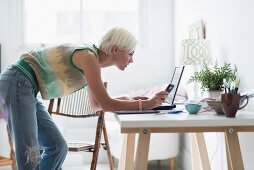 Woman using laptop and cell phone at home