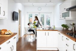 Kitchen-dining room with white fitted cupboards and wooden work surfaces; mother and son in dining area in background