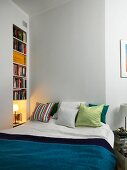 Scatter cushions on double next to bookcase in niche and bedside lamp