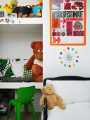 Child's bed below clock on wall next to fitted shelves of cushions and toys in niche
