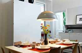 Dining table set with striped beakers and vase of flowers below pendant lamp in dining room