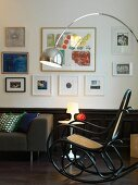 Retro arc lamp above Thonet rocking chair, Tulip table, , couch and gallery of artworks on wall above wainscoting