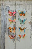 Colourful paper butterflies on wooden board with peeling paint