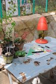 Workspace in greenhouse with tarnished metal table top on wooden trestles and 50s table lamp