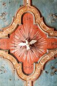 Antique ceiling ornament with religious theme in wood-panelled dining room