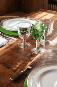 Rustic stem ware and green felt place mats on set farmhouse table