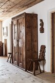 Ornate, antique wooden wardrobe flanked by plank chairs and carved effigy of saint on wall