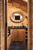 Mirror with oval, wooden frame on rustic wooden wall above washstand with black counter