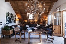 Table, hand-crafted chairs and impressive chandelier in attic living room