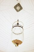Pendant lamp with glass lampshade hanging from white-painted wooden ceiling