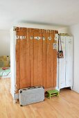 Old wardrobe and white metal lockers used as partition; numbers painted on back of wooden wardrobe with vintage suitcase and green footstool on floor