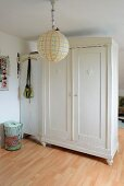 White-painted wardrobe and locker used as partition behind brightly painted paper lampshade