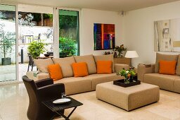 Elegant, beige sofa set with orange scatter cushions and brown leather armchair in front of terrace doors