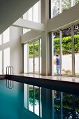 Indoor pool in contemporary house with double-height glass facade and view of garden