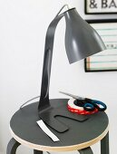 A black retro table lamp on a matching stool with a pair of scissors and sticky tape next to it