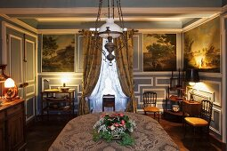 Elegantly furnished dining room with blue and white wood panelling and antique paintings