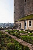 Terrace garden with geometric beds adjoining house built against historical tower facade