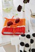 Gestrickte Buchhülle aus verschiedenen Orangetönen und Sonnenbrille auf weißem Tisch