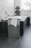 A chrome plated box with a cushion as a combined stool and laundry basket in front of a bubble jet bathtub against a natural stone wall made from decorative facing strips contrasting with the smooth, black tiles on the floor