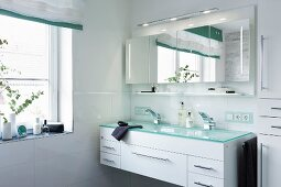 A double wash basin with a turquoise glass platter over a white cupboard with an illuminated, four-door mirrored cabinet