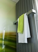 Green and white towels hanging from a rail on a stainless steel towel dryer in a shower area in a modern bathroom
