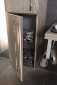 A tall, oak-effect cupboard with stainless steel handles with the lower door open to show towels; floor and wall covered in brown quiet tiles to match the furniture