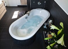 A relaxing looking, water-filled bathtub positioned at an angle in the room with modern taps and and overflow in a dark brown tone