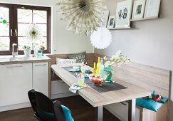 A dining area with a robust, grey-beige wooden look with a corner bench and child's highchair in an open plan kitchen