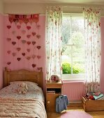 Girl's bedroom in romantic, country-house style with floral bed cover and curtains; wall hanging with heart-shaped pendants on pink wall