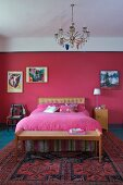 Chandelier above art nouveau bed and bedroom bench with cane seat; small painting on wall painted raspberry and pink bedspread