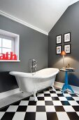 Elegant bathroom with side table and gallery of pictures next to claw-foot bathtub