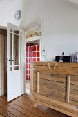 Rustic sideboard with wooden board front next to open door with view of cabinet with small, red doors in hallway