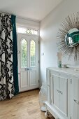 Sunburst mirror above vintage cabinet, front door with stained glass transom light and curtain with classic pattern
