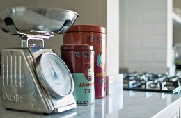 Retro kitchen scales next to Chinese tea caddies on marble kitchen counter in country-house interior