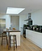 Rustic bar stools at breakfast bar below skylight in modern kitchen