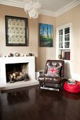 Brown leather armchair next to open fireplace in corner of room painted pale brown with dark wooden floor